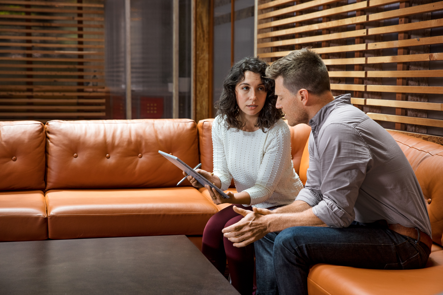 Sales rep and customer sitting on office couch talking
