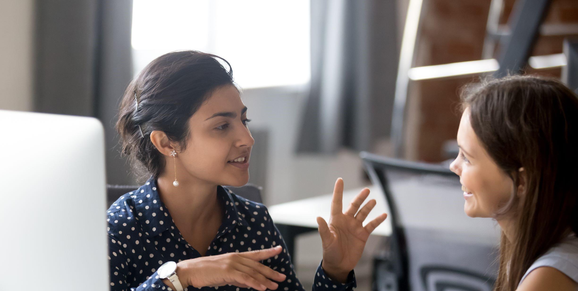 Two women talking at an office desk