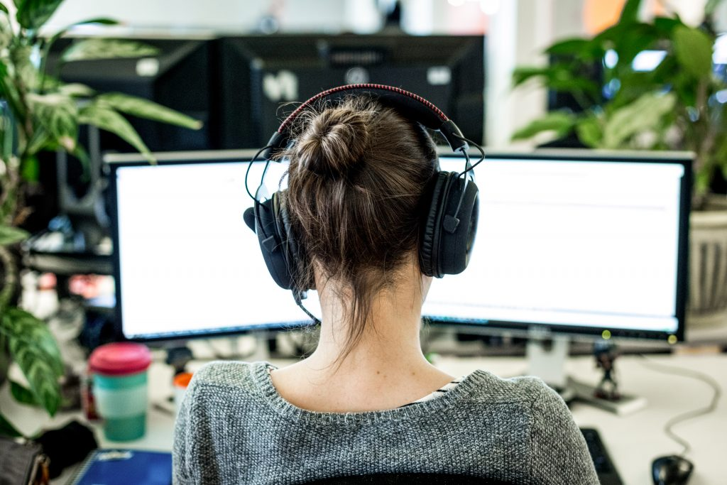 Employee with headphones at a computer