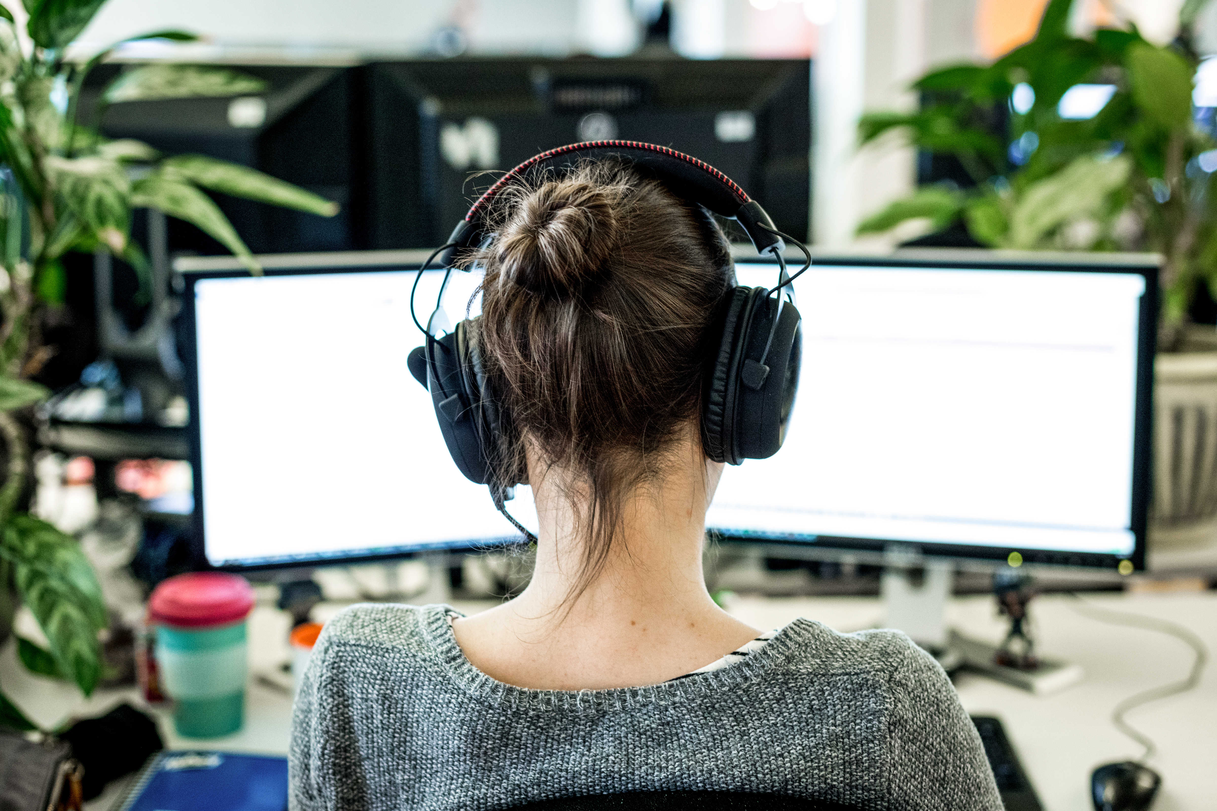 Employee wearing headphones and sitting at a desk with two display screens