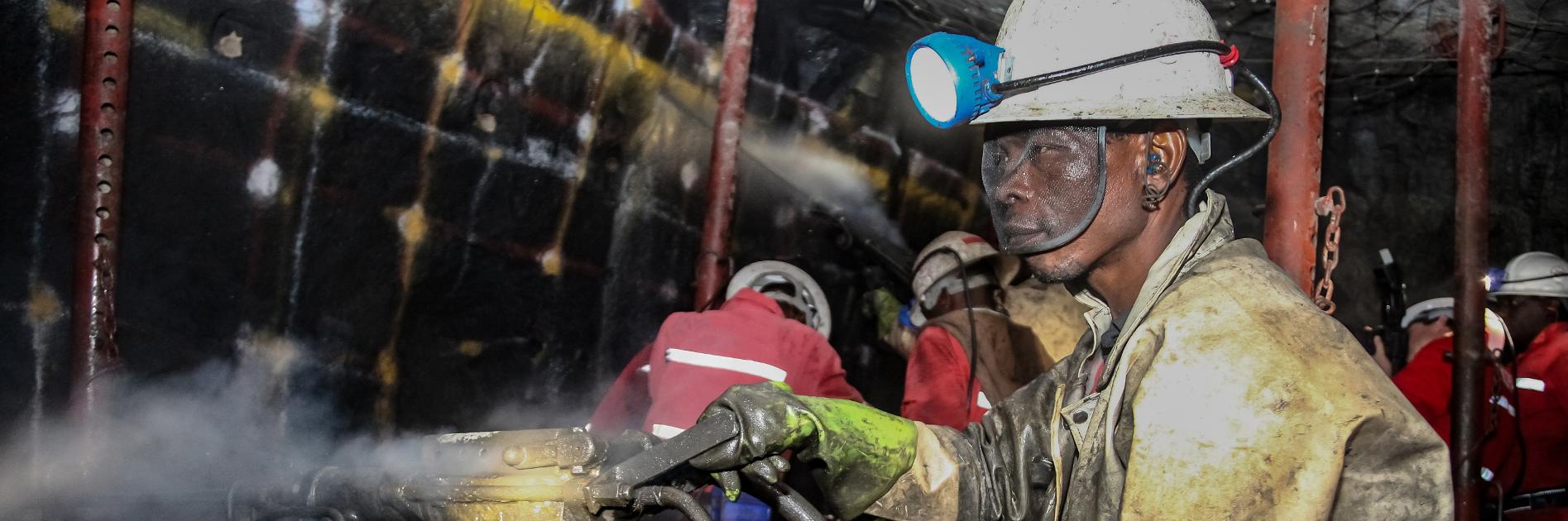 Mining worker holding equipment