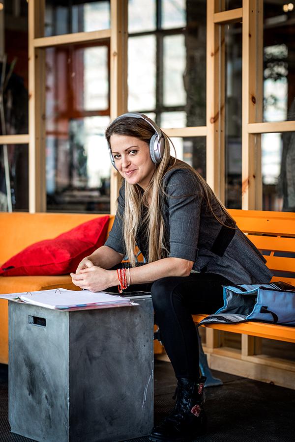 Woman wearing headphones in front of an open binder