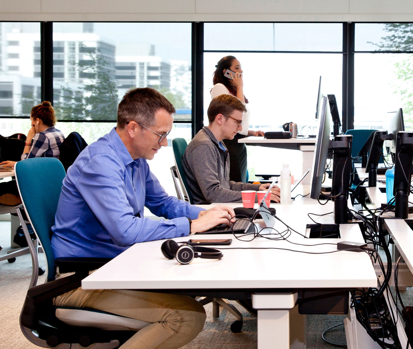 people working on the computer and answering phones in the office