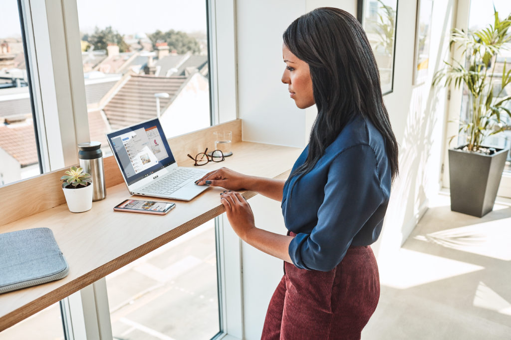 Woman standing and working on a laptop by a large window